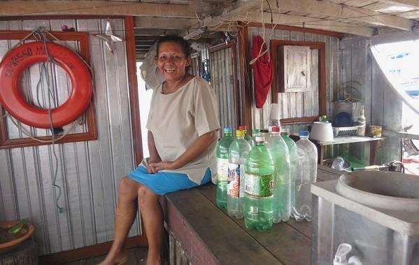 A comandante de barco Estônia Gomes ao lado de garrafas de água que ela compra para beber. (Foto: Elaíze Farias)