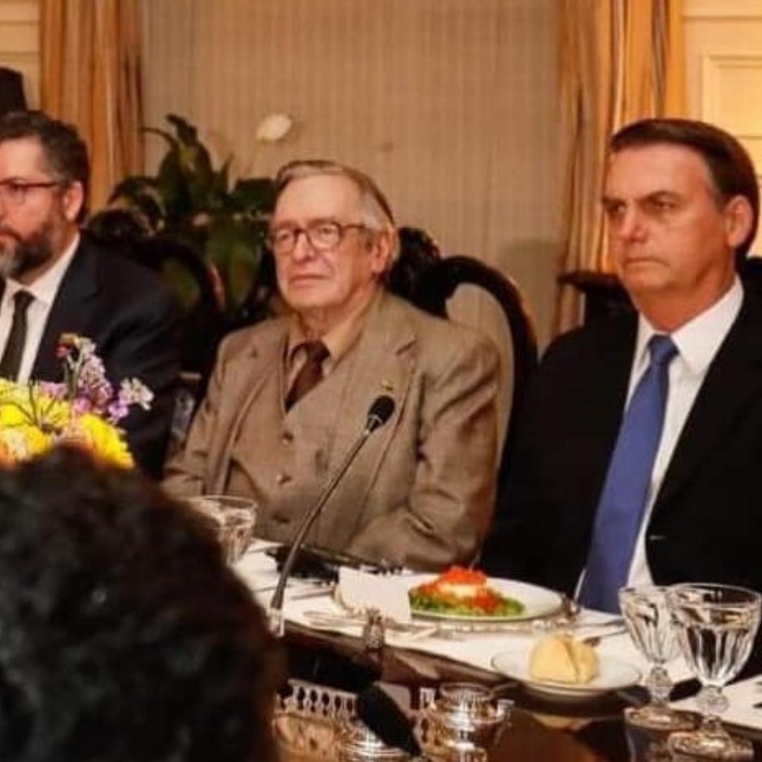 Senhor branco com óculos e terno marrom, Olavo de Carvalho, posa ao lado do presidente Jair Bolsonaro, homem branco de terno preto e gravata azul