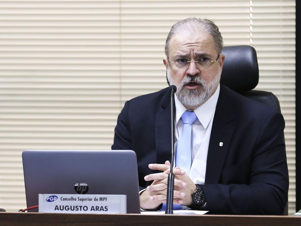 Augusto Aras é um homem branco com cabelo e barba grisalhas. Veste terno preto com gravata azul.